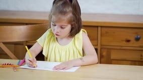 Mała dziewczynka w żółtej sukni z kredkami rysuje na papierze zbiory wideo