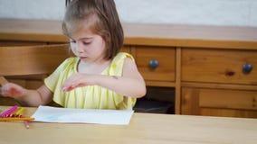 Mała dziewczynka w żółtej sukni z kredkami rysuje na papierze zdjęcie wideo