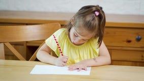 Mała dziewczynka w żółtej sukni z ołówkiem rysuje na papierze zdjęcie wideo