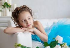 Mała dziewczynka w błękit sukni lying on the beach na kanapie Fotografia Royalty Free