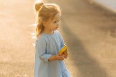 Mała dziewczynka w błękit sukni spacerze w parku zdjęcia stock