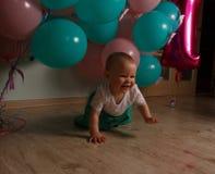 Mała dziewczynka w błękitnej i białej sukni obok balonów, ono uśmiecha się, wakacje, rok, urodzinowy dziecko Siedzi na podłoga kr zdjęcie stock