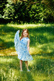 Mała dziewczynka w błękitnej sukni w rękach w lato ogródzie Obraz Stock