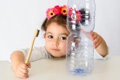 Mała dziewczynka w białego koszulowego mienia bambusowym toothbrush i plastikowej butelce obrazy royalty free