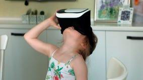 Mała dziewczynka w białym koszulowym dopatrywania 360 wideo w domu, będący ubranym VR słuchawki zdjęcie wideo