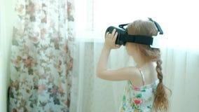 Mała dziewczynka w białym koszulowym dopatrywania 360 wideo w domu, będący ubranym VR słuchawki zbiory wideo
