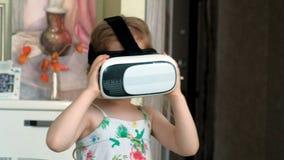 Mała dziewczynka w białym koszulowym dopatrywania 360 wideo w domu, będący ubranym VR słuchawki zbiory