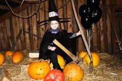 Mała dziewczynka w czarnym Halloween kapeluszu i czarnej odzieży z banią Fotografia Stock