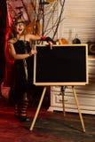 Mała dziewczynka w czarownika kapeluszowym punkcie przy ogłoszenie deską na Halloween Mała dziewczynka w czarownika kontuszu z sz obraz stock