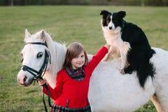 Mała dziewczynka w czerwieni sukni Pies na horseback Mały biały konik obraz stock