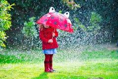 Mała dziewczynka w czerwonej kurtce bawić się w jesień deszczu Zdjęcie Stock