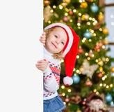 Mała dziewczynka w czerwonym Santa kapeluszu za białą deską Przestrzeń dla teksta Obrazy Stock