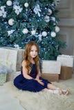 Mała dziewczynka w eleganckiej sukni obsiadaniu przy choinką Obrazy Royalty Free