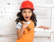 Mała dziewczynka w hełmie z młotem i śrubokrętem fotografia stock