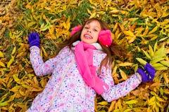 Mała dziewczynka w jesień parka lying on the beach na liście Obraz Royalty Free