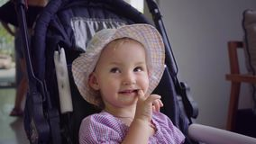 Mała dziewczynka w kapeluszu siedzi w błękitnym spacerowiczu i liże jej usta z jej ręką, zwolnione tempo zdjęcie wideo