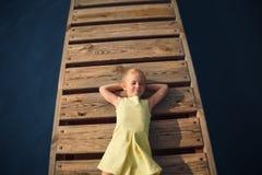 Mała dziewczynka w kolor żółty sukni lying on the beach przy drewnianym molem z zamkniętym okiem Zdjęcie Stock