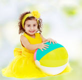 Mała dziewczynka w kolor żółty sukni z dużą piłką Obrazy Stock