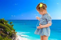 Mała dziewczynka w krótkiej błękit sukni na dennym tle Fotografia Stock