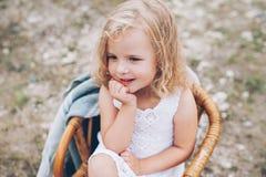 Mała dziewczynka w krześle outdoors Zdjęcia Royalty Free
