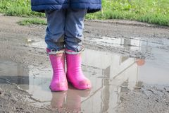 Mała dziewczynka w menchiach inicjuje stojaki w kałuży fotografia stock