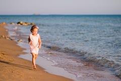 Mała dziewczynka w menchiach ubiera bieg na plaży przy zmierzchem Widok w ruchu Szczęście, wakacje, zabawa szczęśliwy śliczny dzi Obrazy Royalty Free