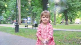 Mała dziewczynka w menchii sukni łapie mydlanych bąble, zwolnione tempo zbiory wideo
