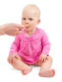 Mała dziewczynka w menchii sukni je od łyżki Obrazy Stock