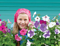 Mała dziewczynka w ogródzie na tle turkusu ogrodzenie Obrazy Stock
