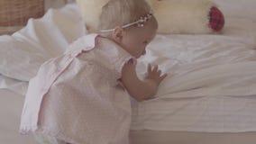 Mała dziewczynka w pieluszce bawić się samotnie na łóżku w domu Uroczy dziecko próbuje dostawać jej cieki w menchii ubraniach zdjęcie wideo