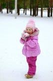 Mała dziewczynka w różowej kurtce bawić się z śniegiem Zdjęcia Stock