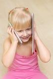 Mała dziewczynka w różowym smokingowym uśmiechu i opowiadać na telefonie komórkowym i Obrazy Royalty Free