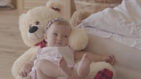 Mała dziewczynka w różowym sukni i pieluszki lying on the beach na niedźwiadkowej zabawce na łóżku w domu, dźwiganie cieki w górę zdjęcie wideo