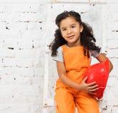 Mała dziewczynka w repairman mundurze z hełmem w rękach obraz royalty free