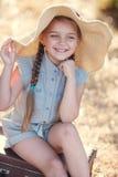 Mała dziewczynka w słomianym kapeluszu, odpoczynkowy obsiadanie na walizce Zdjęcie Stock