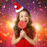 Mała dziewczynka w Santa kapeluszu z cukierek trzciną Święta tła blisko czerwony czasu Obraz Royalty Free