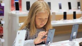 Mała dziewczynka w sklepie używa telefon zdjęcie wideo