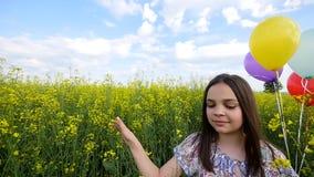Mała dziewczynka w smokingowym bieg przez żółtego pszenicznego pola z balonami w ręce Zwolnione tempa zdjęcie wideo
