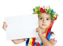 Mała dziewczynka w tradycyjnego ukraińskiego kostiumu mienia odzieżowej papce fotografia stock