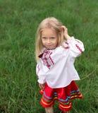 Mała dziewczynka w ukraińskim krajowym kostiumu bawić się z jej h zdjęcie stock