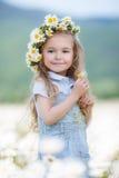 Mała dziewczynka w wianku białe stokrotki zdjęcie stock
