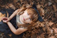 Mała dziewczynka w wizerunku koty siedzi na suchych liściach zdjęcia stock