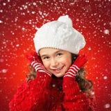 Mała dziewczynka w zimy odzieży, myśl o Santa Czerwony tło Obrazy Stock