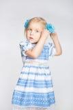Mała dziewczynka wiąże jej włosy w ogonie obraz stock
