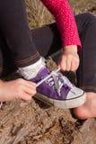 Mała dziewczynka wiąże shoelaces Obraz Stock