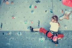 Mała dziewczynka wspina się rockową ścianę Zdjęcie Royalty Free