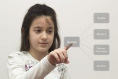 Mała dziewczynka wybiera grę Obrazy Royalty Free