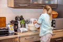 Mała dziewczynka wypiekowi gofry w kuchni po przepis na smartphone obrazy stock