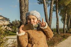 Mała dziewczynka z śmieszną buziak twarzą i popielatą czapeczką bierze selfie Obraz Stock