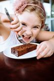 Mała dziewczynka z cappuccino i deserem w kawiarni Dziecko siedzi przy cukiernianym ` s stołem ręce 14 dni ojciec dziecka emocje  zdjęcia stock